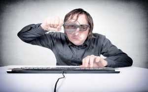 Guy with magnifying glass peeping at passwords
